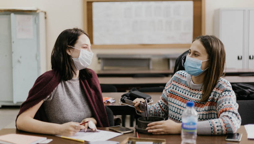 Two students wearing masks in class