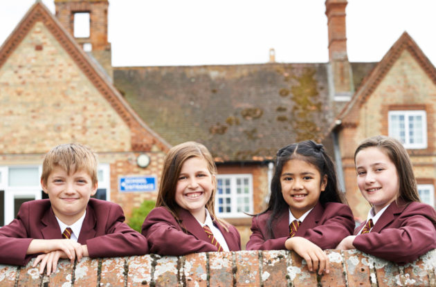Four school kids in uniform leaning on a wall smiling